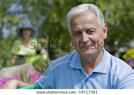 Senior man with his wife in the background