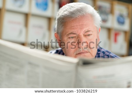Senior man with mustache reading newspaper in library