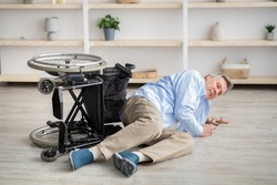 Senior man with physical disability lying on floor after falling down from his wheelchair at home