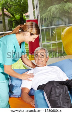 Senior man with physiotherapist doing remedial exercises