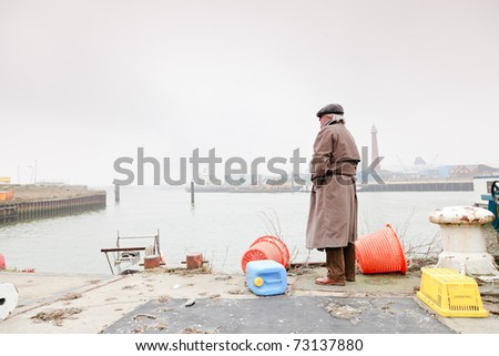 Senior man with raincoat and hat standing in dock. Lonely. Lost.