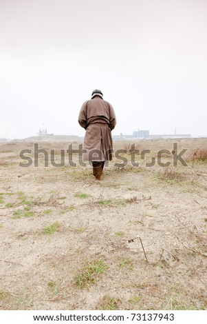 Senior man with raincoat and hat walking on sand with grass. Open space. Lost.