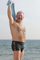 Senior man with towel on a beach after sea bathing