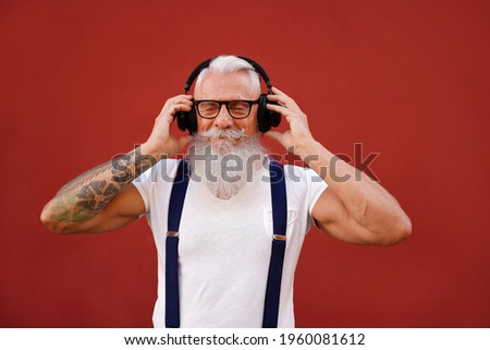 Senior man with white beard and mustache listening favorite music with headphones. People happy lifestyle and technology concept. Red background. Fashionable mature men.        ストックフォト ©