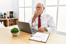 Senior man working at the office using computer laptop bored yawning tired covering mouth with hand. restless and sleepiness.