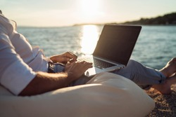 Senior man working on his laptop on the beach during sunset. Close up