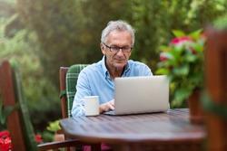 Senior man working on laptop in the garden