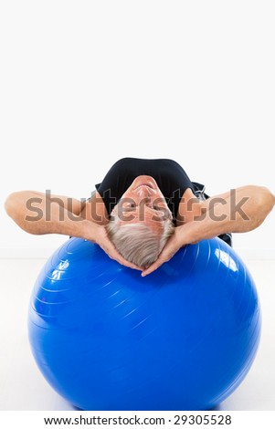 senior man working out on fitness ball and looking at camera. Copy space