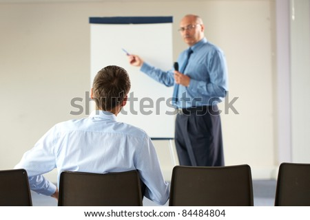 senior manager during seminar, presentation, point to white board and hold microphone, indoor shoot