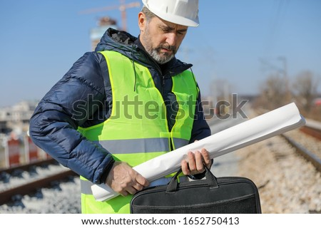 Senior manager in white helmet safety stands pencil and blueprint for architect engineer at site checking project structure with cement pillars,