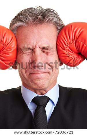 Senior manager pushing red boxing gloves against his aching head