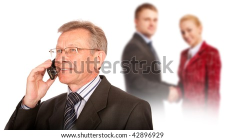 Senior manager talks by mobile phone against partners shaking hand.