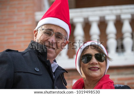 senior married couple pose with a pope noel cap in the garden of their home Foto stock ©