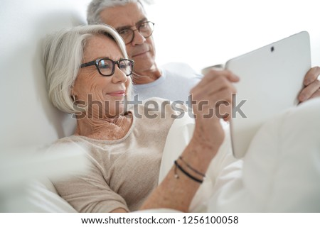 Senior married couple relaxing in bed looking at tablet