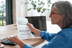 Senior mature business woman holding paper bill using calculator, old lady managing account finances, calculating money budget tax, planning banking loan debt pension payment sit at home office table.