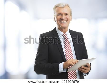 Senior (mature) businessman standing and holding a digital tablet in his hand