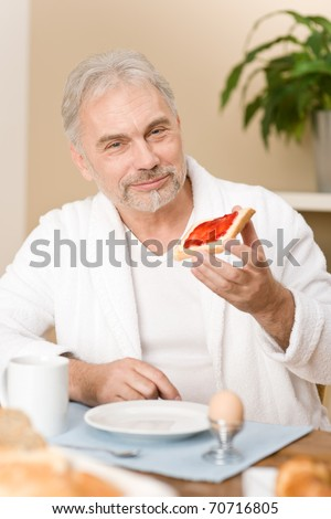 Senior mature man - breakfast at home with orange juice, coffee and egg