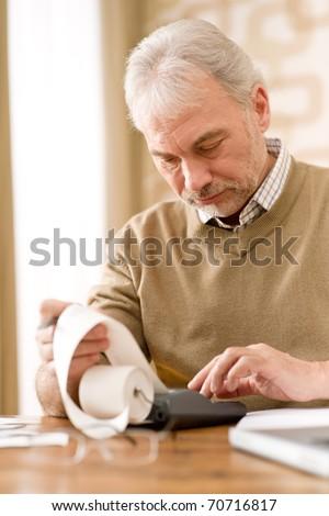 Senior mature man - home office using paper tape calculator
