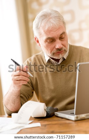 Senior mature man - home office using paper tape calculator and laptop