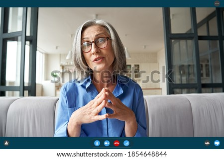 Senior mature old woman online teacher, remote tutor, distance coach talking to web cam virtual counseling conference video calling at home office. Web cam view. Videocall app screenshot screen view