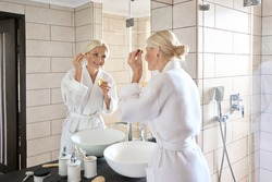 Senior mature older caucasian woman applying face eye contour treatment with antiaging pipette serum essence oil looking at mirror wearing bathrobe. Bright complexion skin care products advertising.