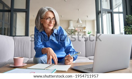 Senior mature older senior adult professional business woman working on laptop from home office, having virtual video call meeting, watching online training webinar e learning class using computer.
