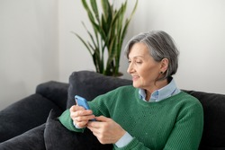 Senior mature woman wearing a green jumper, sitting on the couch in the living room, holding a mobile phone, and waiting for the application to be installed, spending time on social media