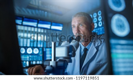 Senior Medical Research Scientist Looking under the Microscope in the Laboratory. Neurologist Solving Puzzles of the Mind and Brain. In the Lab with Multiple Screens Showing MRI / CT Brain Scan Images