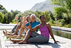 Senior men and mature women doing yoga exercise near swimming pool outdoor. Multiethnic people in a row practicing stretching exercise. Group of middle aged sporty people practicing pilates lesson.