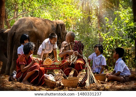 Senior Men and women are weaves basket with nephew and granddaughter and a big elephant in the forest. Old man and woman weaves bamboo basket or fish trap with elephant in forest. Surin, Thailand. #1480331237