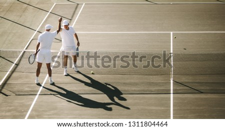 Senior men playing tennis on a sunny day. Tennis players greeting each other after a game of tennis.
