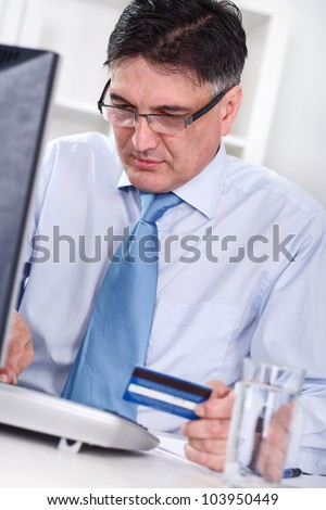 Senior men sitting front computer with credit card , ready for shopping on-line