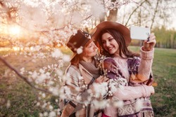 Senior mother and her adult daughter hugging and taking selfie in blooming garden. Mother's day concept. Family values