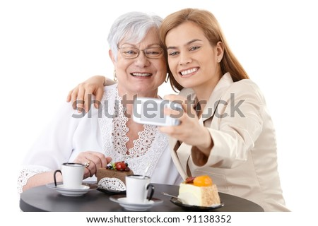Senior mother and young daughter sitting at coffee table, photographing themselves by digital camera, smiling happily.?