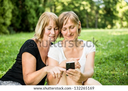 Senior mother showing on mobile phone to her adult child - outdoor in nature