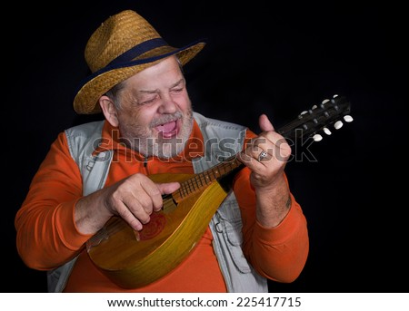 Senior musician with mandolin playing and singing country music on a stage