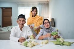 senior muslim couple and daughter making ketupat for eid fitr mubarak celebration at home