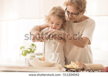 Senior nanny helping child to break the egg into a bowl