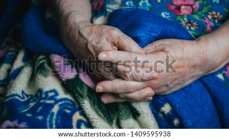 Senior old hands and arms. blue background. fingers, nails with veins. wrinkled skin of aged person. aging process.