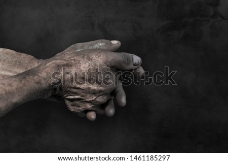 Senior old hands and arms.fingers and nails with veins. wrinkled skin of aged person. aging process.hand dirty of worker after working on dark background