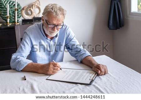Senior old man elderly examining and signing last will and testament