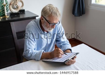 Senior old man elderly reading and examining reverse mortgage application form
