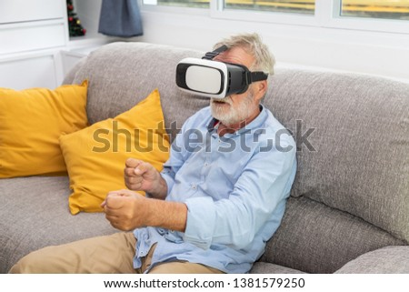 Senior old man eldery enjoy playing game with VR Virtual Reality goggle on couch sofa