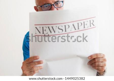 Senior old man reading newspaper.