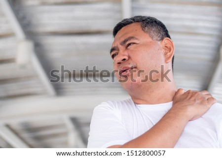 senior old man suffering from shoulder pain or injury