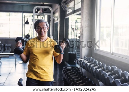 Senior old man working out with heavy weight dumbbells by two hands with exercise machines background in fitness gym. Bodybuilding and healthy happy lifesytle for 60s elderly guy.