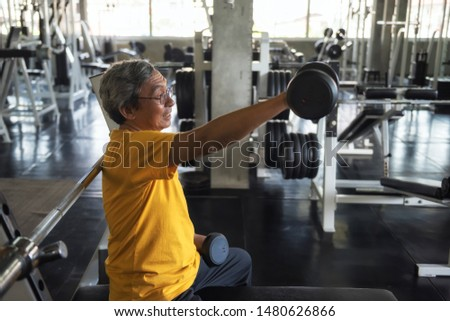 Senior old man working out with heavy weight dumbbells with exercise machines background in fitness gym. Bodybuilding and healthy happy lifesytle for 60s elderly guy.