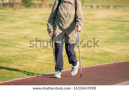 senior old people walking in the morning on the city running road, doing slow jogging for health