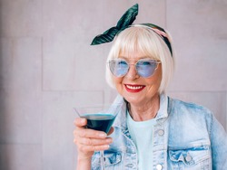 senior (old) stylish woman with gray hair and in blue glasses and denim jacket holding glass with blue cocktail. Alcohol, relax, holidays, retirement concept