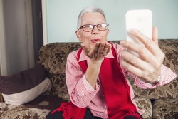 Senior old woman sending love and kisses to her family over skype or viber using her cellphone